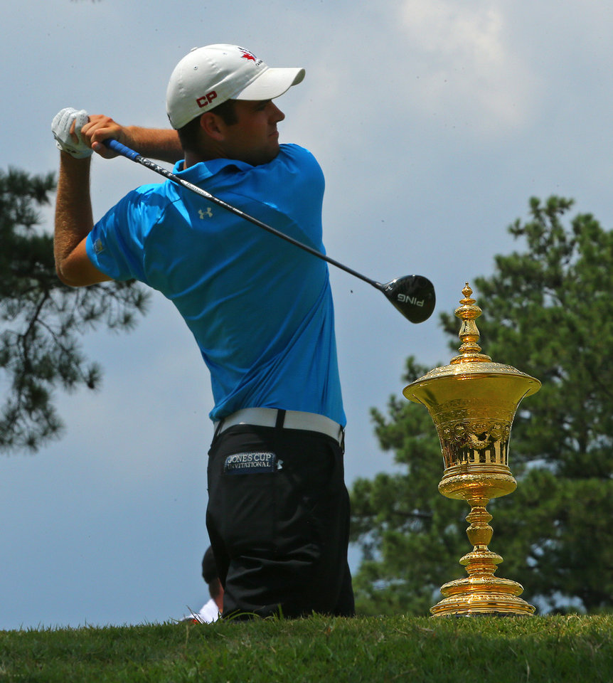 Photo - The trophy sits on the tee box as Corey Conners, of Canada, tees off on the first hole during the 2014 U.S. Amateur Championship at Atlanta Athletic Club on Sunday, Aug. 17, 2014, in Johns Creek, Ga. (AP Photo/Atlanta Journal-Constitution, Curtis Compton)  MARIETTA DAILY OUT; GWINNETT DAILY POST OUT; LOCAL TV OUT; WXIA-TV OUT; WGCL-TV OUT