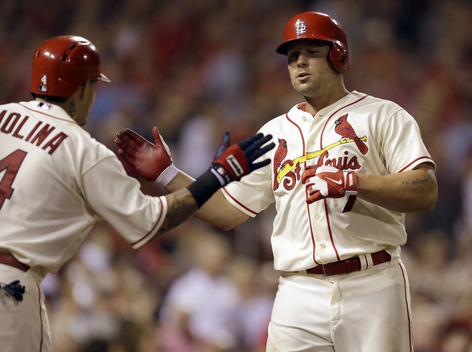 Photo - St. Louis Cardinals' Matt Holliday, right, is congratulated by teammate Yadier Molina after hitting a solo home run during the eighth inning in the second baseball game of a doubleheader against the Chicago Cubs Saturday, Aug. 30, 2014, in St. Louis. The home run was Holliday's second of the game. (AP Photo/Jeff Roberson)