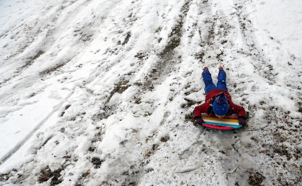 Photo - Turner Kinzer sleds down a hill at Hafer Park in Edmond, Okla., Tuesday, Feb. 12, 2013.Photo by Sarah Phipps, The Oklahoman