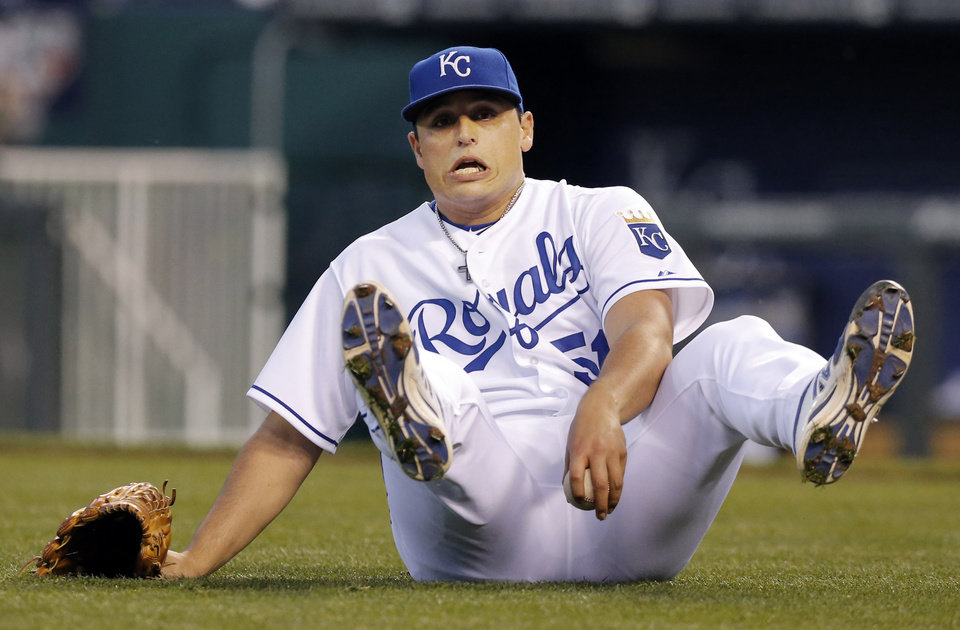 Photo - Kansas City Royals starting pitcher Jason Vargas falls while fielding a ground ball hit by Minnesota Twins' Brian Dozier during the third inning of a baseball game at Kauffman Stadium in Kansas City, Mo., Friday, April 18, 2014. Dozier was safe at first base on the play. (AP Photo/Orlin Wagner)