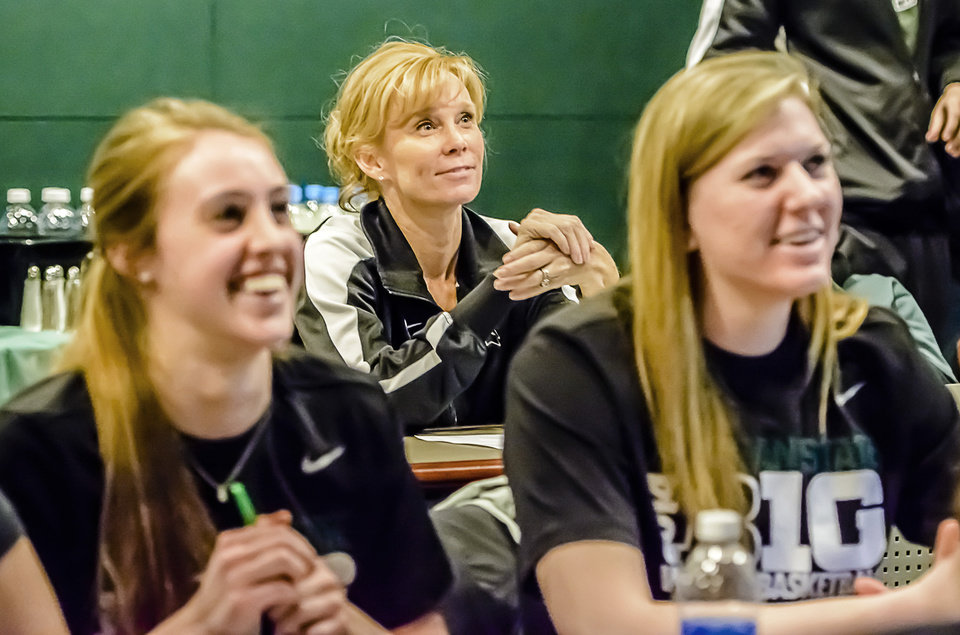Photo - Michigan State University Women's Basketball Head Coach Suzy Merchant, center,  smiles as the MSU Women's Basketball team NCAA bracket is announced Monday March 17, 2014.  The team and staff watched the broadcast of the selections at the Breslin Center in East Lansing, Mich.  (AP Photo/The State Journal, Kevin W. Fowler)  NO SALES