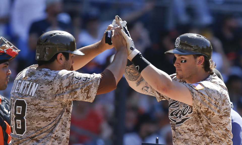 Photo - San Diego Padres' Yasmani Grandal, right, is greeted by teammate Carlos Quentin after hitting a two-run home run against the San Francisco Giants in the eighth inning of a baseball game on Sunday, July 6, 2014, in San Diego. (AP Photo/Lenny Ignelzi)