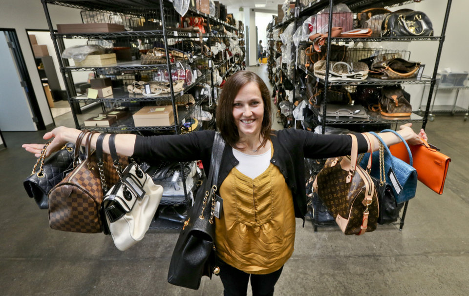 This photo taken May 2, 2013, shows Sarah Davis, co-owner of Fashionphile.com, posing with her bags in a company warehouse in the Carlsbad, Calif. The Internet company sells rare, vintage, and discontinued previous owned bags and is facing the complicated task of dealing with new state regulations on Internet sale taxes. (AP photo/Lenny Ignelzi)