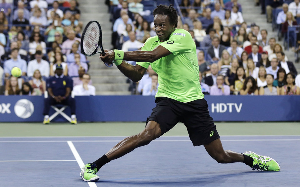 Photo - Gael Monfils, of France, slides as he returns to Roger Federer, of Switzerland, during the quarterfinals of the U.S. Open tennis tournament, Thursday, Sept. 4, 2014, in New York. (AP Photo/Charles Krupa)