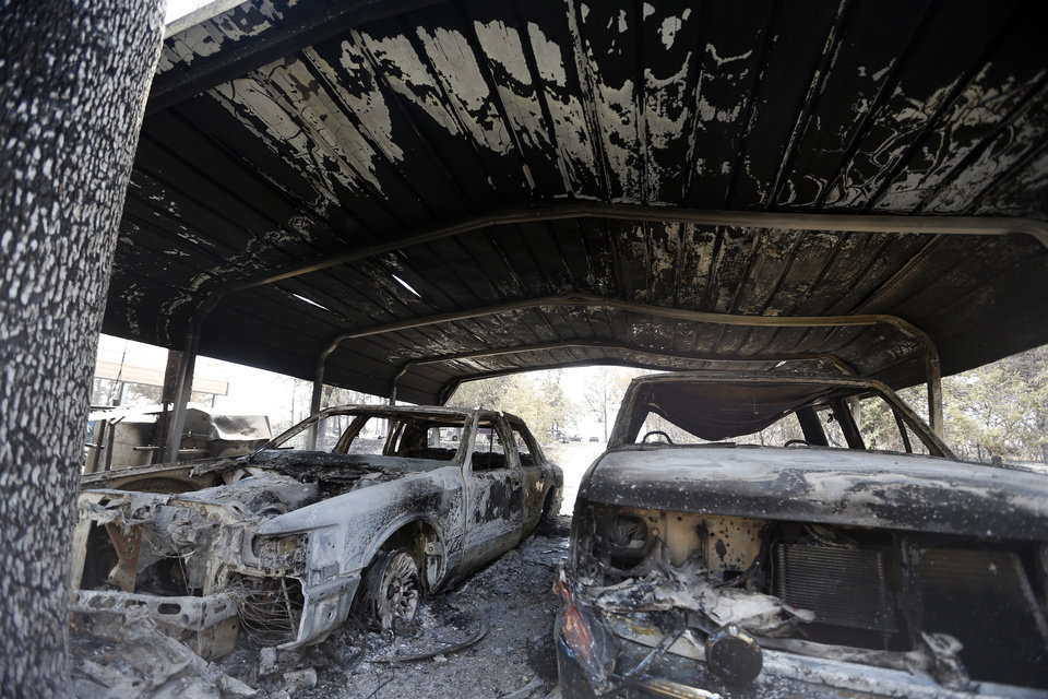 Photo - Burned cars are pictured , Sunday, Aug. 5, 2012, in the community of Oak Grove near Drumright, Okla., after wildfires moved through the area Saturday. Photo by Sarah Phipps, The Oklahoman