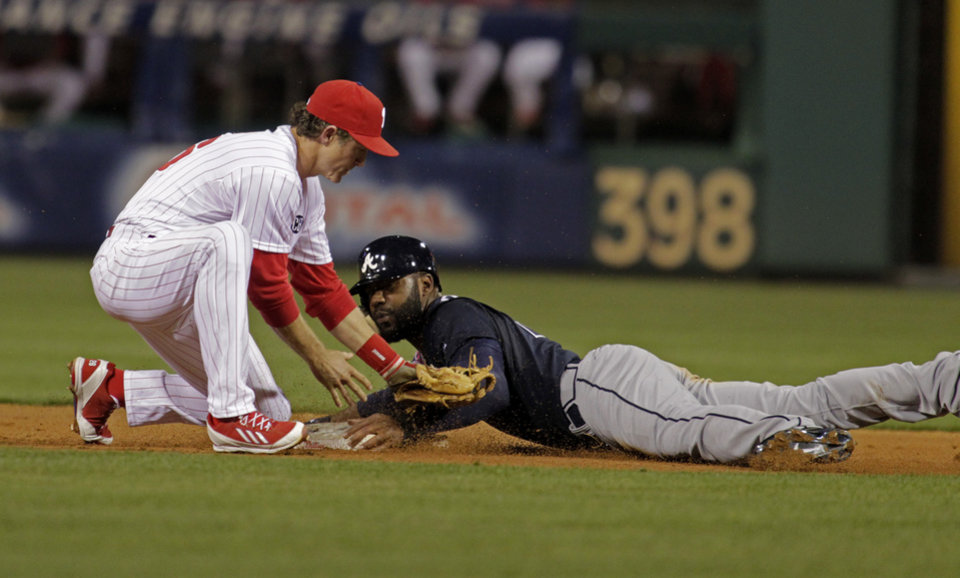 Photo - Atlanta Braves' Justin Upton right, steals second as Philadelphia Phillies' Chase Utley makes a late tag in the third inning of a baseball game Monday, April 14, 2014, in Philadelphia.  (AP Photo/H. Rumph Jr)