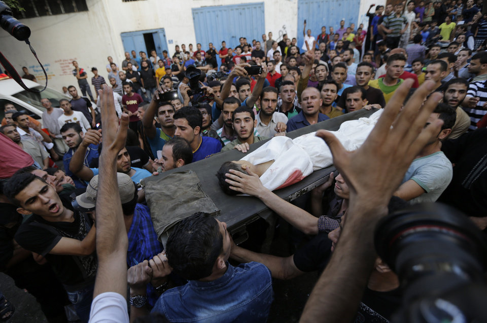 Photo - Palestinians chant slogans as mourners carry the body of Muhammed Abu Shagfa, 7, killed in an explosion, during the funeral in Shati refugee camp, in the northern Gaza Strip, Monday, July 28, 2014. An explosion killed 10 people, 9 of them children, at a park at Shati refugee camp, in northern Gaza Strip. Israeli and Palestinian authorities traded blame over the attack and fighting in the war raged on despite a major Muslim holiday. (AP Photo/Lefteris Pitarakis)