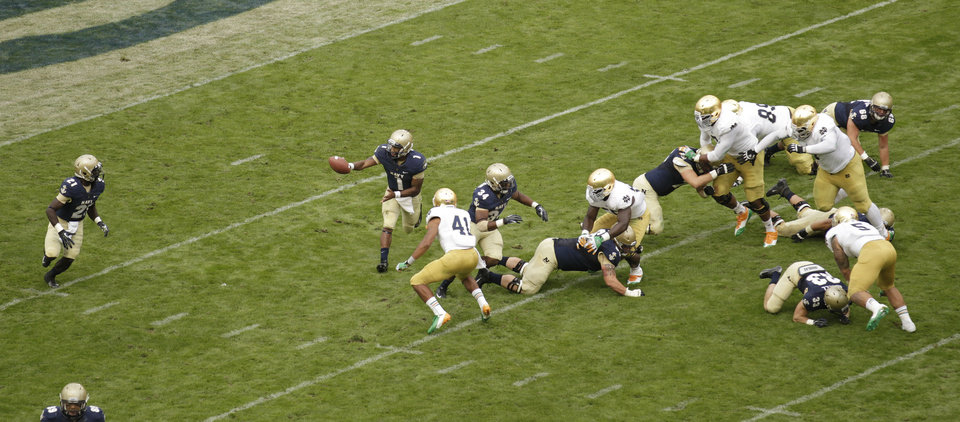 Photo -   Navy quarterback Trey Miller, center, passes the ball to Gee Gee Greene, left, while playing against Notre Dame during their NCAA college football game in Dublin, Ireland, Saturday, Sept. 1, 2012. (AP Photo/Peter Morrison)