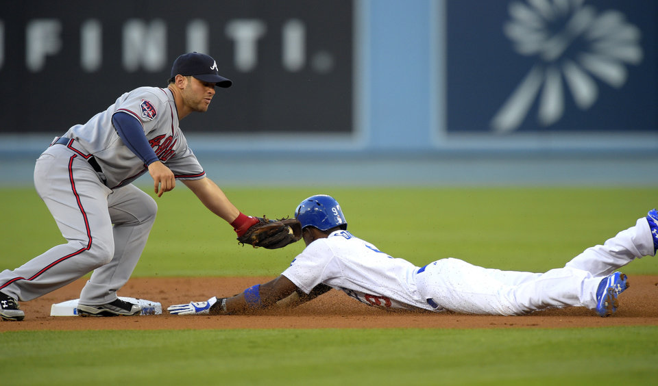 Photo - Los Angeles Dodgers' Dee Gordon, right, is caught stealing second by Atlanta Braves second baseman Tommy La Stella during the first inning of a baseball game, Thursday, July 31, 2014, in Los Angeles. (AP Photo/Mark J. Terrill)