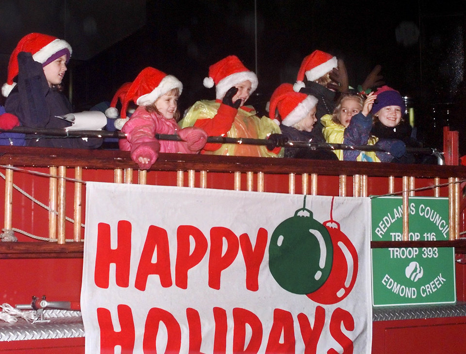 December 1999: Girls representing Girl Scout Daisy Troop 393 and Brownie Troop 116 from Edmond Creek wave to the crowd while riding on a vintage firetruck in the downtown Oklahoma City Festival of Lights Christmas parade Saturday evening. PHOTO BY JIM BECKEL, THE OKLAHOMAN