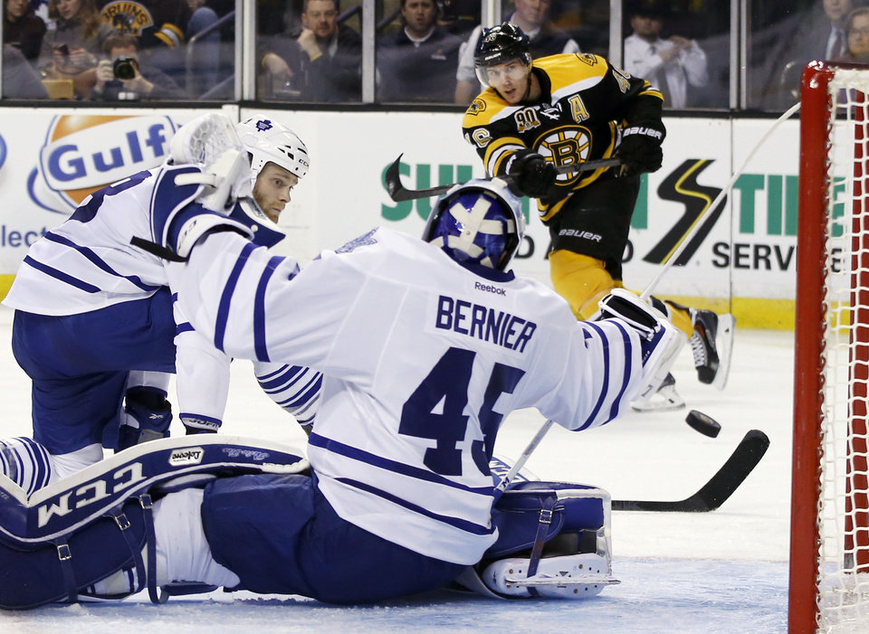 Photo - Toronto Maple Leafs defenseman Tim Gleason, left, watches as goalie Jonathan Bernier (45) defends the net on a shot by Boston Bruins center David Krejci (46), which passes through the crease in the second period of an NHL hockey game in Boston, Tuesday, Jan. 14, 2014. (AP Photo/Elise Amendola)