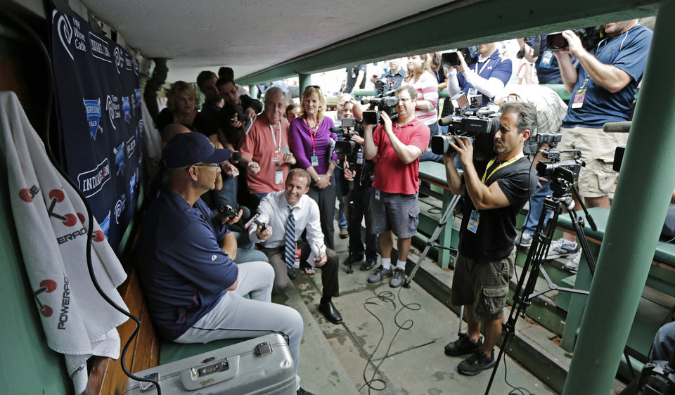 Photo - Cleveland Indians manager Terry Francona, left, is surrounded by members of the media in the visitor's dugout before a baseball game against the Boston Red Sox at Fenway Park in Boston, Thursday, May 23, 2013. Francona was Red Sox manager for the 2004 and 2007 World Series Championship seasons. (AP Photo/Charles Krupa)