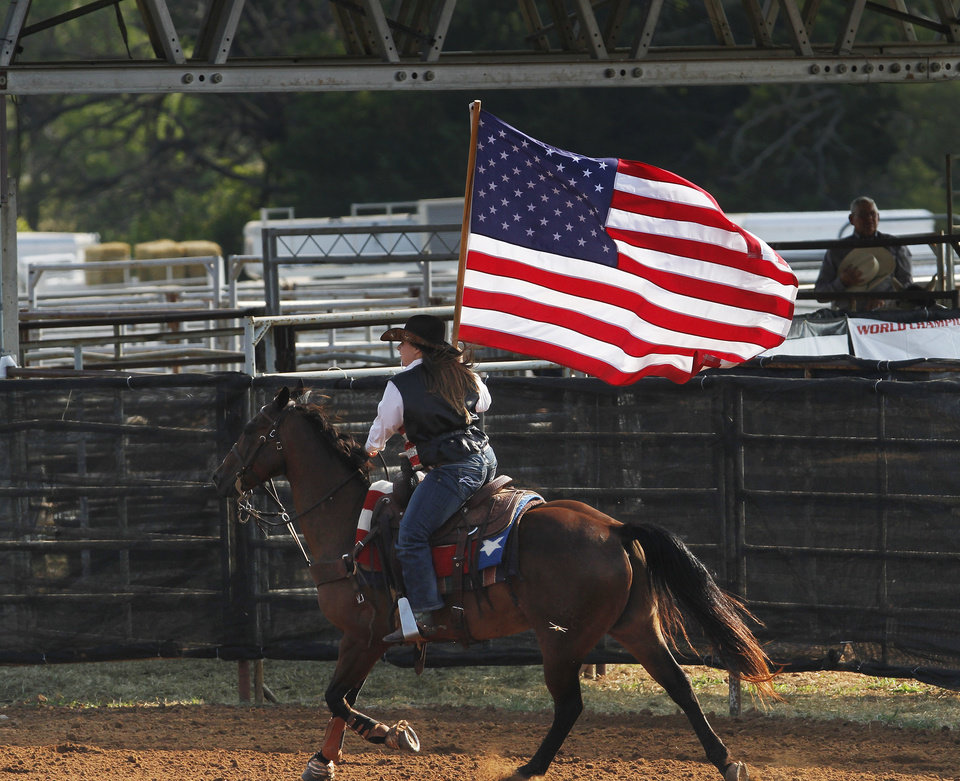 Colby Hall, 15, of Tecumseh, Okla., carries an American flag around one of the arenas before the start of the second go-round of the International Finals Youth Rodeo at the Heart of Oklahoma Exposition Arena in Shawnee, Okla., on Monday, July, 9, 2012. Tuesday, July 3, 2012. Hall competes in barrel racing and pole bending events. Photo by Jim Beckel, The Oklahoman