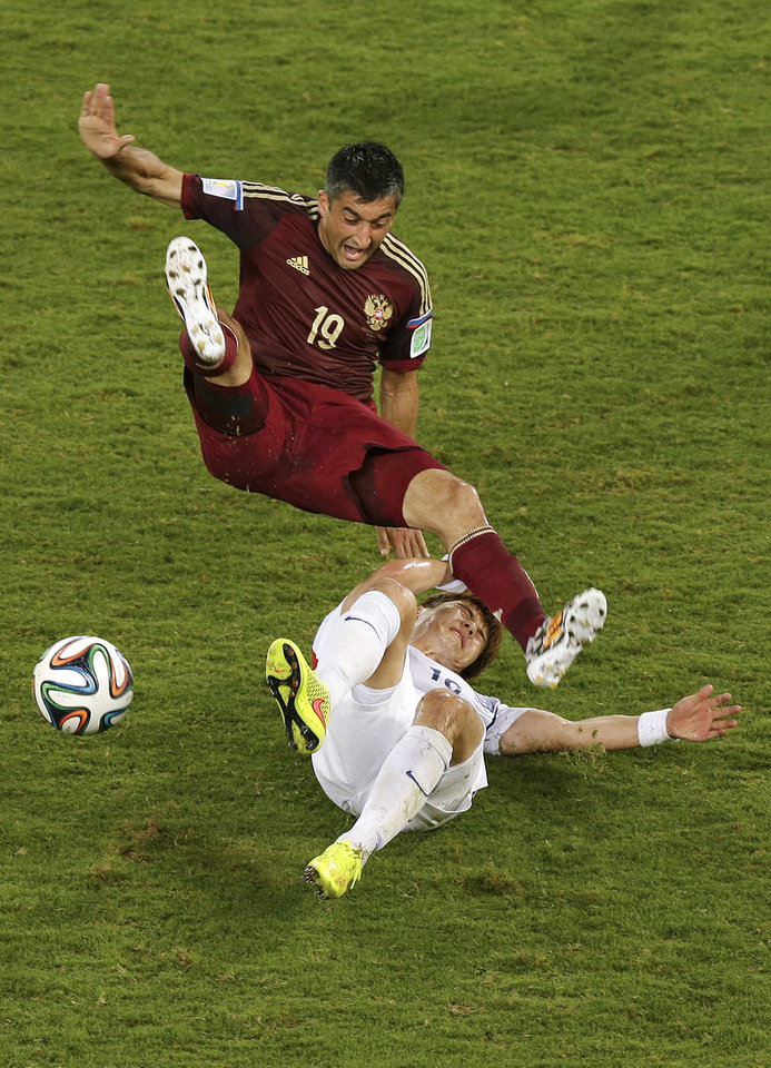 Photo - South Korea's Ki Sung-yueng, bottom, fouls Russia's Alexander Samedov (19) during the group H World Cup soccer match between Russia and South Korea at the Arena Pantanal in Cuiaba, Brazil, Tuesday, June 17, 2014. (AP Photo/Thanassis Stavrakis)