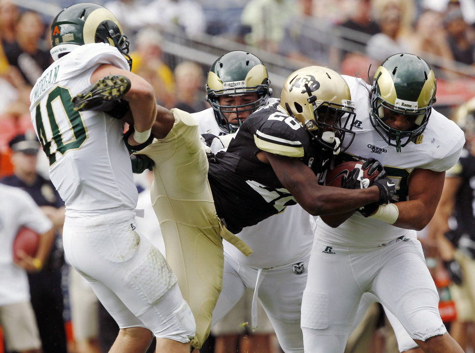 Photo -   Colorado tailback Tony Jones, center, is tackled by, from left, Colorado State defenders Max Morgan, Alex Tucci and Eli Edwards in the first quarter of an NCAA college football game in Denver on Saturday, Sept. 1, 2012. (AP Photo/David Zalubowski)