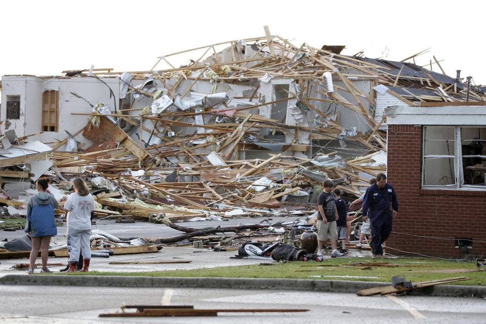 Photo - Residents and others walk by the remains of the First Baptist Church following a tornado that destroyed the town Wednesday, April 27, 2011 in Smithville, Miss..(AP Photo/Northeast Mississippi Daily Journal, Thomas Wells)