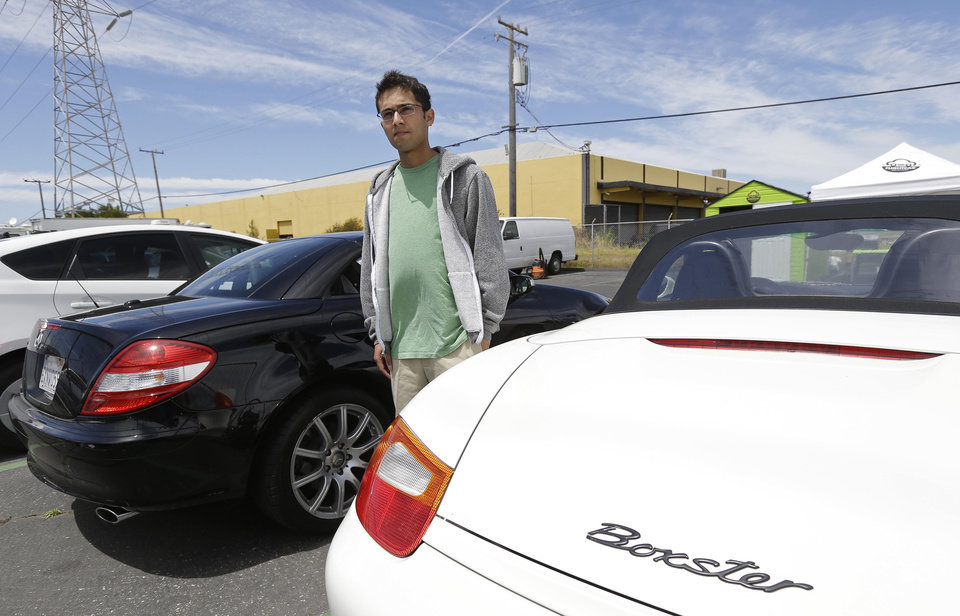 Photo - In this photo taken Tuesday, June 11, 2013 Flightcar CEO Rujul Zaparde, poses on their car lot in Burlingame, Calif. A San Francisco Bay area startup company founded by three teenage Ivy League dropouts is trying to change the airport car rental business. FlightCar rents out people's personal vehicles while they are traveling, giving them a share of the proceeds and free airport parking in exchange. But the company's rosy outlook does have some thorns. San Francisco's City Attorney has sued FlightCar, accusing it of unfair competition. (AP Photo/Eric Risberg)