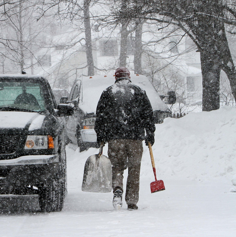 Photo - A man heads out to clear snow as it falls again, Monday, Feb. 11, 2013 in Concord, N.H.  After digging out from two feet of snow over the weekend more snow arrived on Monday. (AP Photo/Jim Cole)