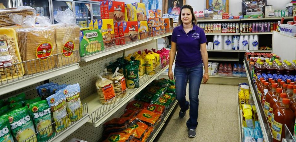 Photo - Ana Mora works in the store that her in-laws have owned and operated on Main Street for six years in the panhandle community of Guymon.
