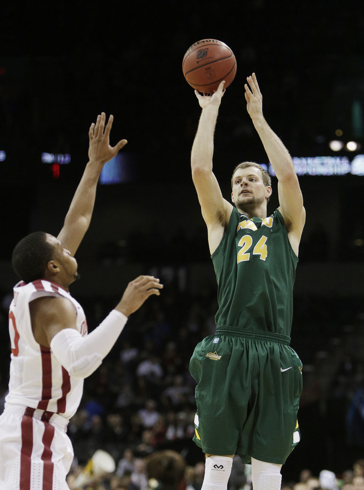 Photo - North Dakota State's Taylor Braun (24) shoots against Oklahoma's Jordan Woodard during the first half of a second-round game of the NCAA men's college basketball tournament in Spokane, Wash., Thursday, March 20, 2014. (AP Photo/Young Kwak)