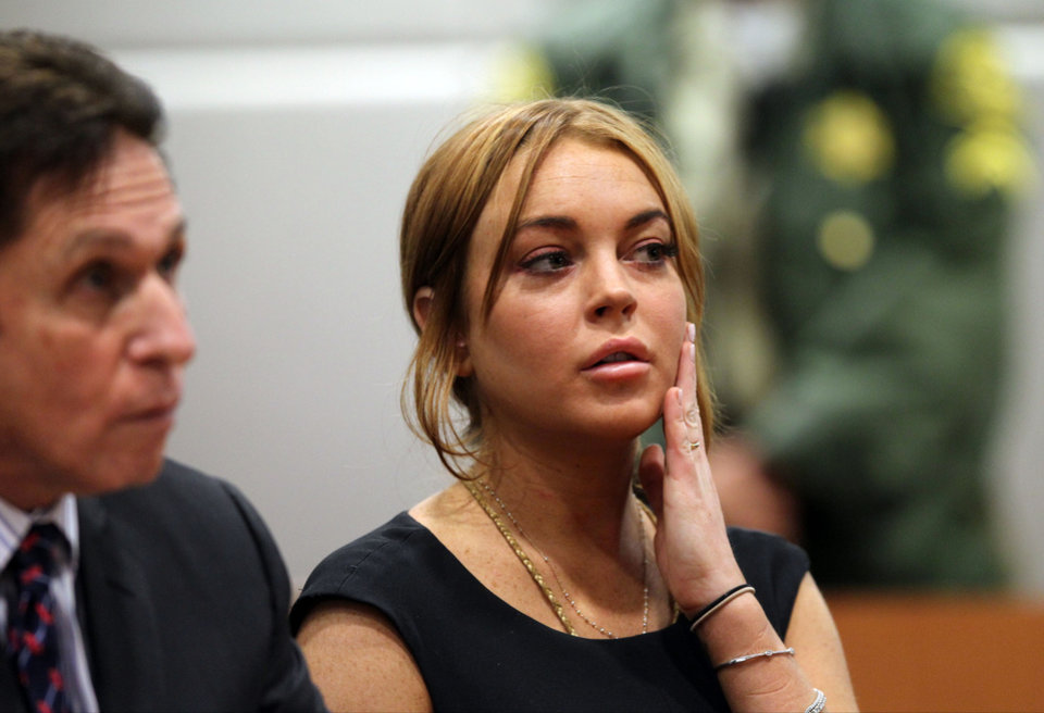 Photo - Actress Lindsay Lohan appears in Los Angeles court with her new attorney Mark Heller, left, for a pretrial hearing, Wednesday, Jan. 30, 2013, in a case filed over the actress' June car crash. Lohan faces three misdemeanor charges and a return to jail if convicted in the case or if a judge finds she violated her probation. (AP Photo/David McNew, Pool)