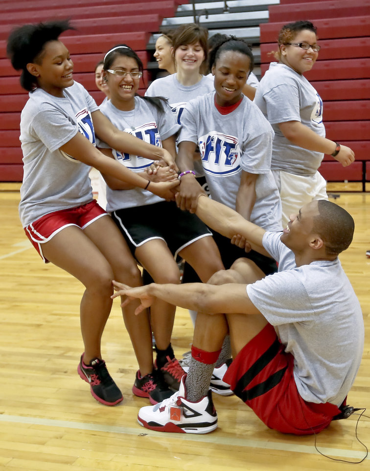 Photo - THUNDER FIT / NBA BASKETBALL TEAM: Russell Westbrook gets some help off the court by Lachina Mitchell, Nina Kopaddy and Ladarius Robinson, from left, after doing some exercises during a visit by the Oklahoma City Thunder to students at U.S. Grant High School to promote physical fitness on Monday, Jan. 28, 2013, in Oklahoma City, Okla.  Photo by Chris Landsberger, The Oklahoman