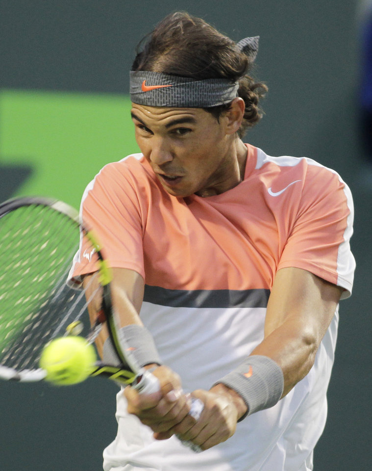 Photo - Rafael Nadal, of Spain, returns the ball to Milos Raonic, of Canada, during the Sony Open tennis tournament, Thursday, March 27, 2014, in Key Biscayne, Fla. (AP Photo/Luis M. Alvarez)