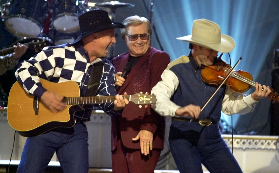 Photo - FILE - In this Nov. 7, 2001 file photo, Garth Brooks, left, and George Jones, center, perform their duet
