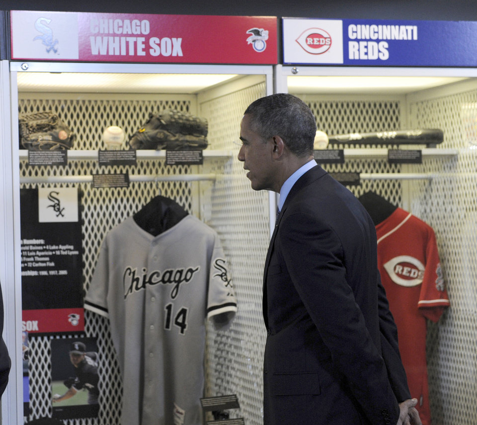 Photo - President Barack Obama looks over a Chicago White Sox exhibit as he tours the Baseball Hall of Fame in Cooperstown, N.Y., Thursday, May 22, 2014. Obama visited the museum to highlight tourism and steps to help spur international visits to the 50 states. Obama said the overall U.S. economy and local businesses will benefit if it isn't a hassle for people from other countries to visit the U.S. and spend money at its hotels, restaurants, tourist destinations and other businesses. (AP Photo/Susan Walsh)