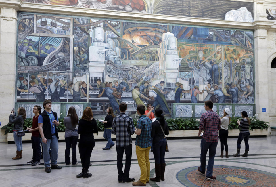 Photo - FILE - In this Dec. 10, 2013, file photo, visitors look at the Detroit Industry murals created by Mexican artist Diego Rivera at the Detroit Institute of Arts in Detroit. The DIA announced Monday, May 5, 2014, that it is planning an exhibition next year that focuses on the year that Rivera and his artist wife Frida Kahlo spent in the city. (AP Photo/Carlos Osorio, File)