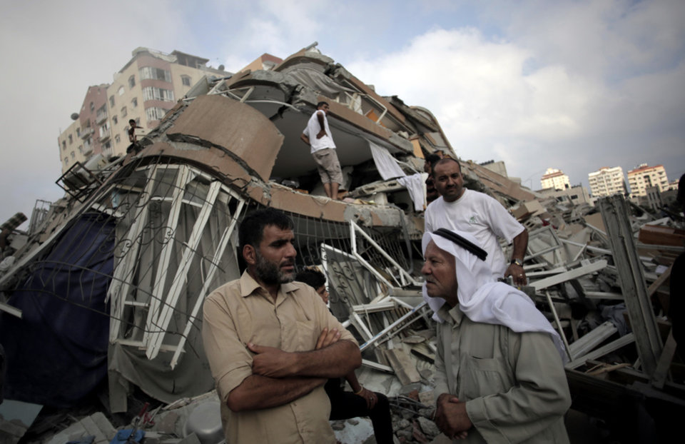 Photo - Palestinians gather near the Al-Zafer apartment tower following Israeli airstrikes Saturday that collapsed the 12-story building, in Gaza City, Sunday, Aug. 24, 2014. The army said the Gaza City apartment tower was targeted because a Hamas command center operated from there. The weekend strikes by Israel marked the first time large buildings were toppled signaling a new escalation in seven weeks of fighting with Hamas. (AP Photo/Khalil Hamra)