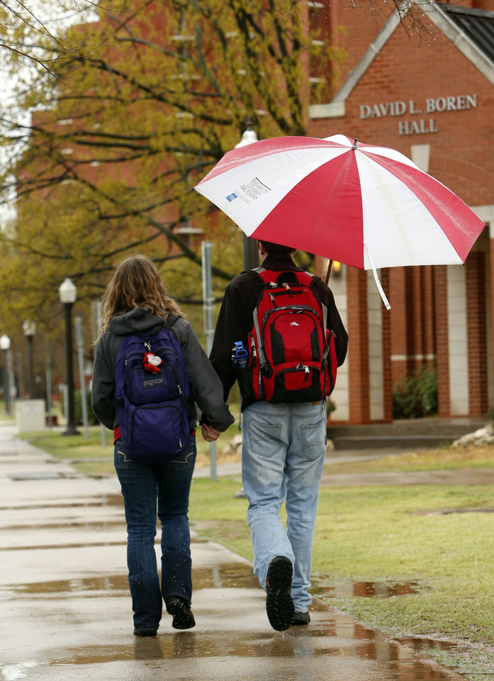 Photo - Students David Barron and Rebecka Bruhn walk past buildings on the campus of the University of Oklahoma on Tuesday, April 2, 2013 in Norman, Okla.  Photo by Steve Sisney, The Oklahoman