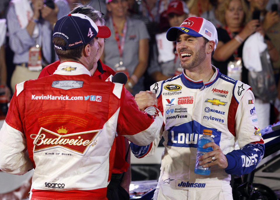 Photo - Jimmie Johnson, right, is congratulated by Kevin Harvick, left, after winning the NASCAR Sprint Cup series Coca-Cola 600 auto race at Charlotte Motor Speedway in Concord, N.C., Sunday, May 25, 2014. (AP Photo/Terry Renna)