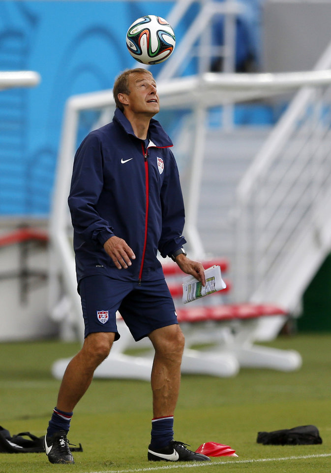Photo - United States' head coach Jurgen Klinsmann heads a soccer ball before an official training session the day before the group G World Cup soccer match between Ghana and the United States at the Arena das Dunas in Natal, Brazil, Sunday, June 15, 2014.  (AP Photo/Julio Cortez)