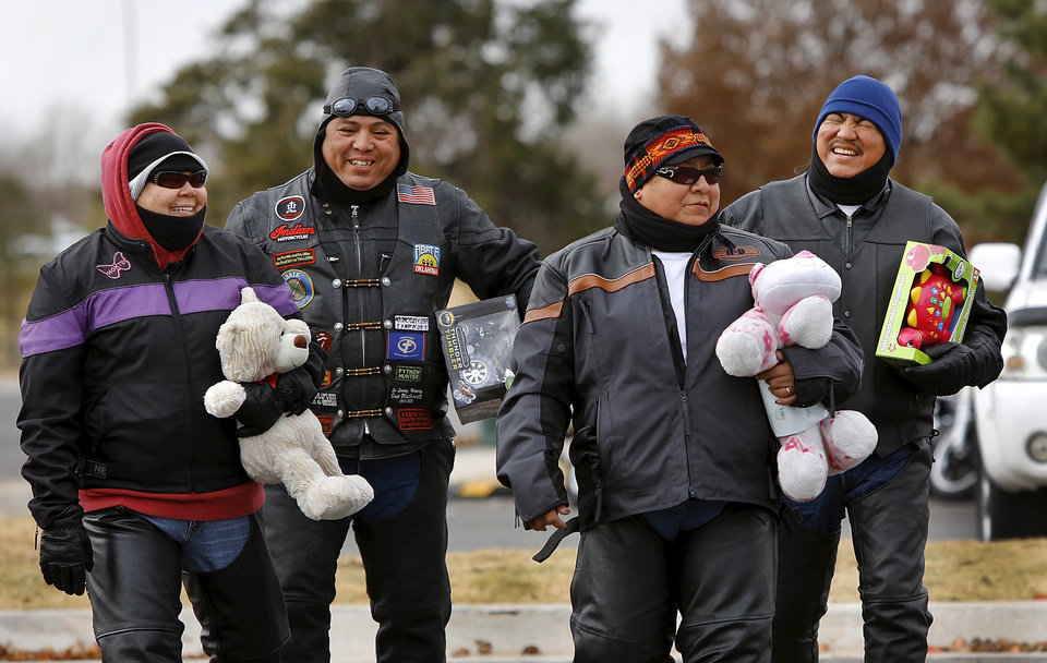 From left, Serena Selumber of Shawnee; Amos Tallbear of Choctaw; Elsie and Henry Sleeper, Oklahoma City, all members of the Oklahoma Indian Bikers Motorcycle Club, carry unwrapped toys to donate. They participated in the charity ride because they wanted to support the motorcycle clubs and help children by donating items to the toy collection. About 300 motorcycle riders participated in a charity ride in southwest Oklahoma City on Sunday afternoon, Dec. 9, 2012. Escorted by Oklahoma City police motorcycle units, the bikers traveled along SW 29 Street, S. Western, SW 44 Street and returned to Woodson Park at SW 36 and S. May Avenue. Feed The Children and the Fellowship of Christian Bikers sponsored the motorcycle ride/toy drive. Photo by Jim Beckel, The Oklahoman