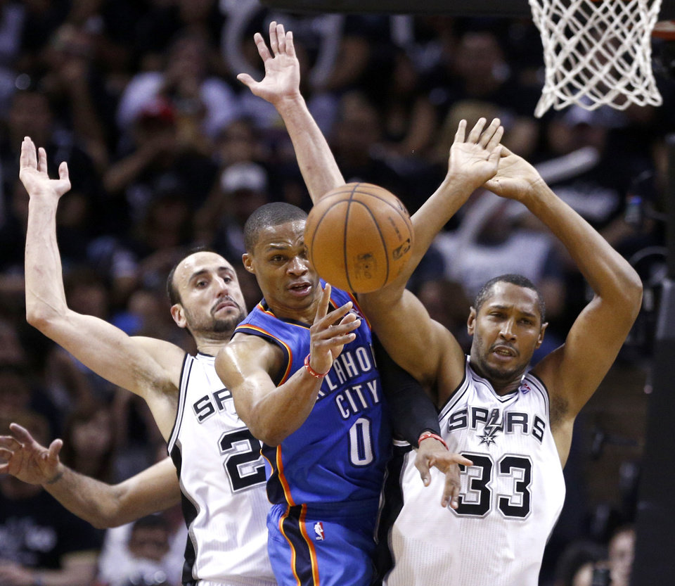 Photo - Oklahoma City's Russell Westbrook (0) looks to pass the ball as San Antonio's Manu Ginobili (20) and San Antonio's Boris Diaw (33) defend during Game 1 of the Western Conference Finals in the NBA playoffs between the Oklahoma City Thunder and the San Antonio Spurs at the AT&T Center in San Antonio, Monday, May 19, 2014. Photo by Sarah Phipps, The Oklahoman