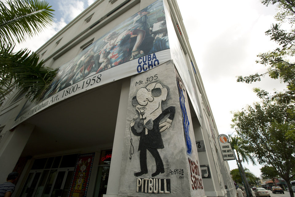 Photo - This May 1, 2014 photo shows a caricature of Cuban–American recording artist Pitbull  on the side of the side of building along Calle Ocho (Eighth Street) in Miami's Little Havana. Once a refuge for Cuban exiles rekindling the tastes and sounds a lost home, today Miami's Little Havana is a mosaic of cultures and a popular tourist destination. (AP Photo/J Pat Carter)