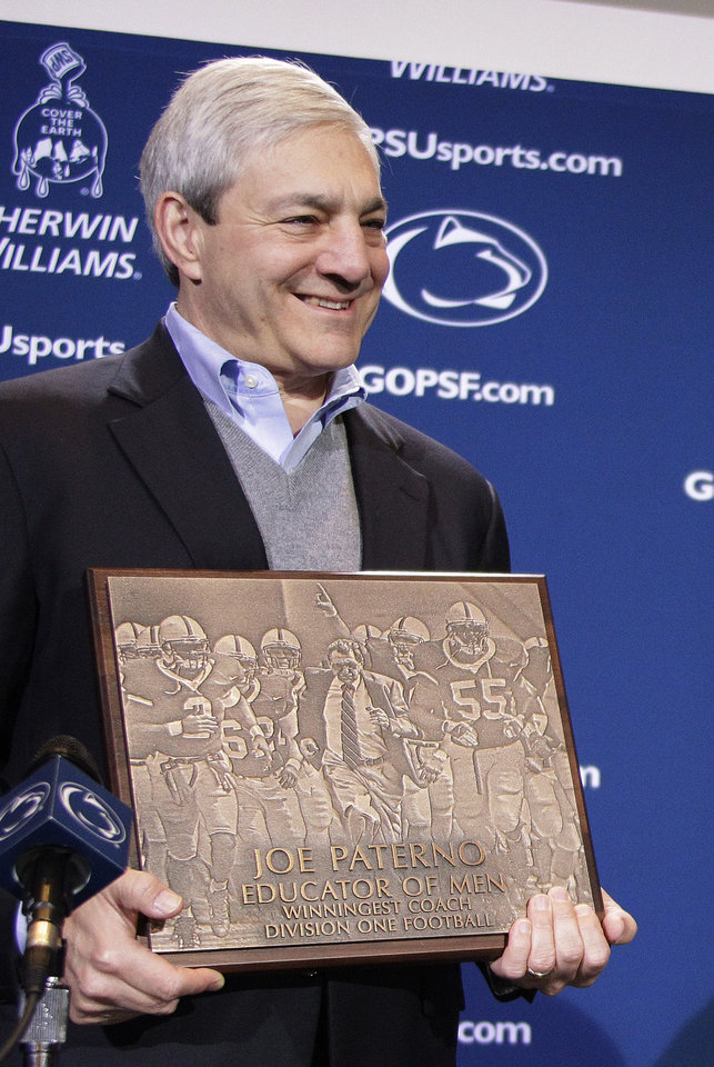 """FILE - In this Oct. 29, 2011 file photo, Penn State President Graham Spanier presents head football coach Joe Paterno with a plague commemorating his 409th collegiate win after an NCAA college football game against Illinois in State College, Pa. Spanier is accused of perjury, endangering children and other charges in the Jerry Sandusky molestation scandal. According to online court records charges were filed, Thursday, Nov. 1, 2012, against Penn State\'s ex-president and two other administrators in what prosecutors called """"a conspiracy of silence."""