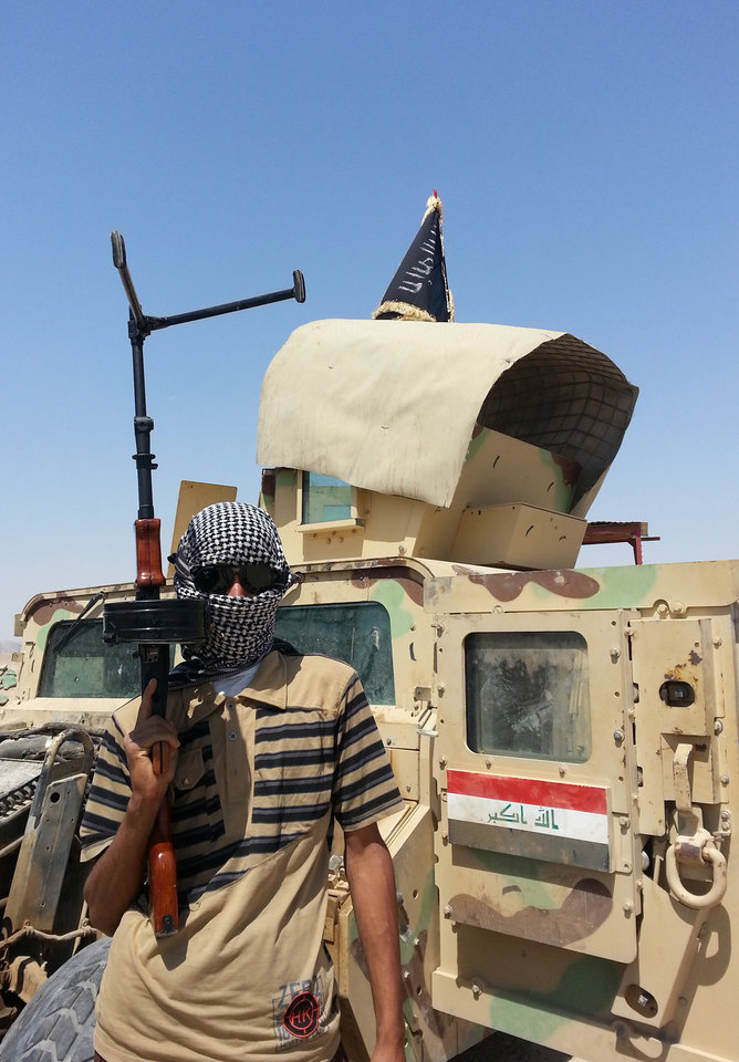 Photo - An al-Qaida inspired militant stands with a captured Iraqi Army Hmvee at a checkpoint outside Beiji refinery, some 250 kilometers (155 miles) north of Baghdad, Iraq, Thursday, June 19, 2014. The fighting at Beiji comes as Iraq has asked the U.S. for airstrikes targeting the militants from the Islamic State of Iraq and the Levant. While U.S. President Barack Obama has not fully ruled out the possibility of launching airstrikes, such action is not imminent in part because intelligence agencies have been unable to identify clear targets on the ground, officials said.(AP Photo)
