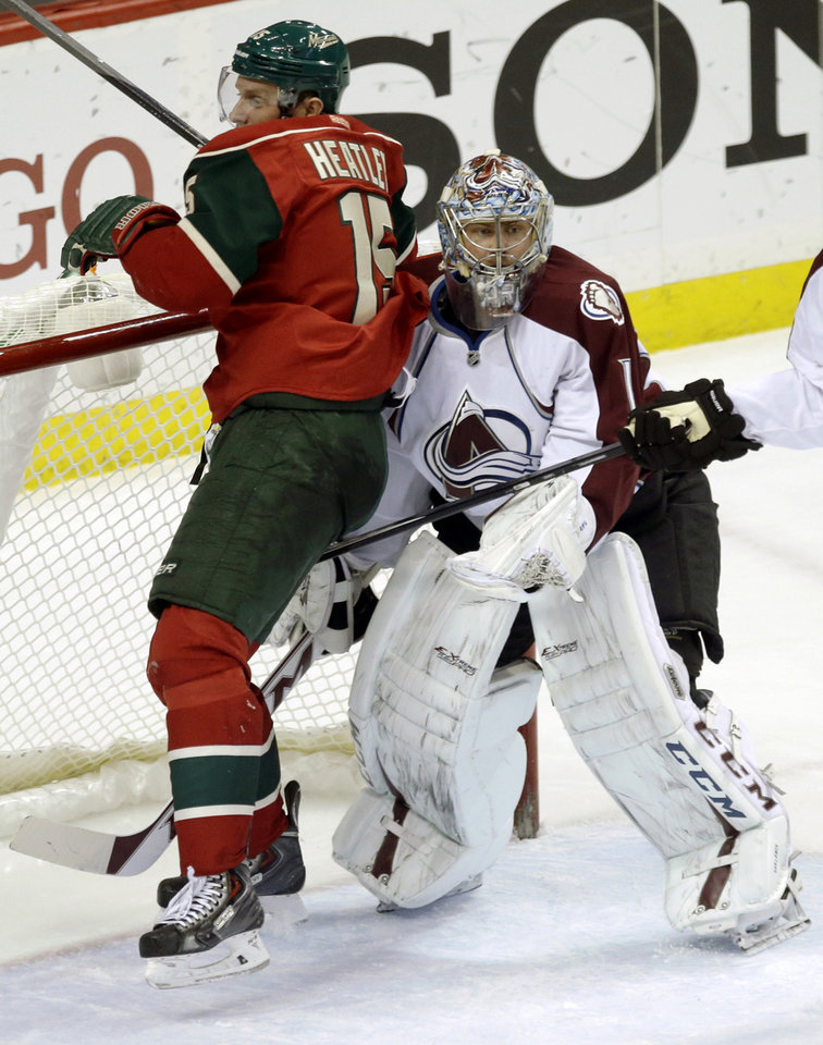 Photo - Colorado Avalanche goalie Semyon Varlamov, right, of Russia, stands by as Minnesota Wild's Dany Heatley crashes into the goal during the first period of an NHL hockey game, Saturday, Jan. 11, 2014, in St. Paul, Minn. (AP Photo/Jim Mone)