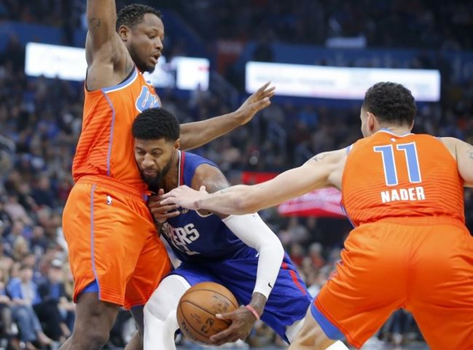 Photo -  Oklahoma City's Deonte Burton (30) and Abdel Nader (11) defend LA's Paul George (13) during Sunday night's game. The Thunder defense limited George to 18 points. [Bryan Terry/The Oklahoman]