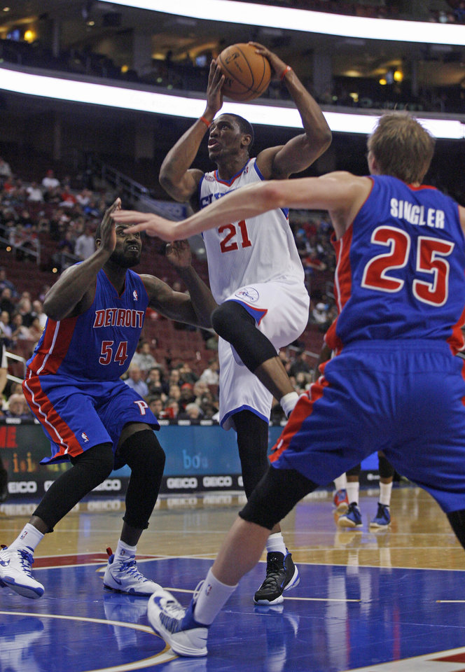 Philadelphia 76ers' Thaddeus Young (21) drives the lane against the Detroit Pistons' Jason Maxiell (54) and Kyle Singler (25) in the first half of an NBA basketball game Wednesday Nov. 14, 2012 in Philadelphia. (AP Photo/ H. Rumph Jr)