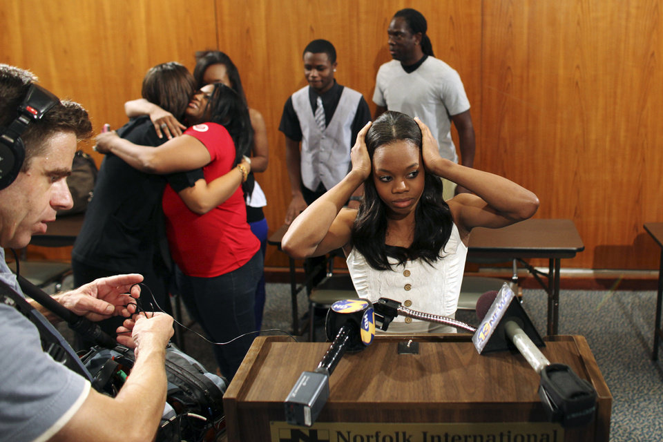 Photo -   Gabby Douglas, 2012 London Summer Olympics gold medal-winning gymnast, prepares for a news conference after arriving at Norfolk International Airport, Thursday, Aug. 16, 2012, in Norfolk, Va., on her way to visit her hometown of Virginia Beach, Va. (AP Photo/Virginian-Pilot, Ross Taylor) MAGS OUT