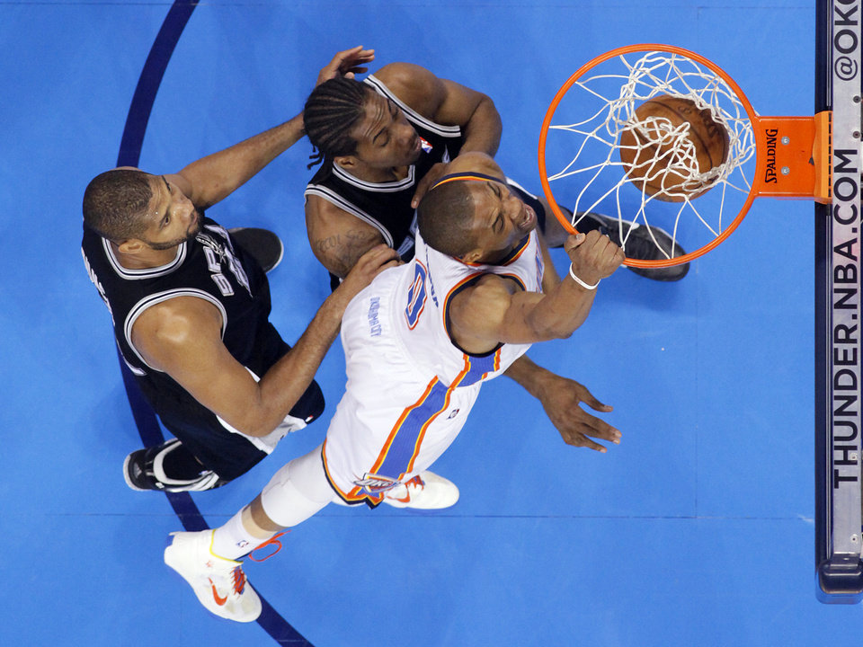 Photo - Oklahoma City's Russell Westbrook (0) dunks over San Antonio's Tim Duncan (21) and Kawhi Leonard (2) during Game 6 of the Western Conference Finals between the Oklahoma City Thunder and the San Antonio Spurs in the NBA playoffs at the Chesapeake Energy Arena in Oklahoma City, Wednesday, June 6, 2012. Photo by Chris Landsberger, The Oklahoman