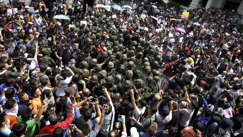 Photo - Thai soldiers are surrounded by anti-coup protesters during a demonstration in Bangkok, Thailand, Sunday, May 25, 2014. Hundreds of protesters in the Thai capital are defying the junta's warning against anti-coup demonstrations with a rally in the central shopping district that's being closely watched by troops. (AP Photo/Sakchai Lalit)