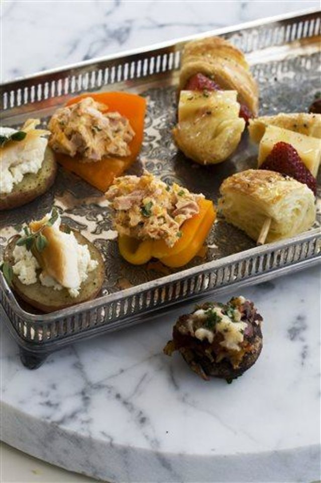 Photo - In this image taken on April 22, 2013, smoked schmeared potatoes, left, a chorizo hash stuffed mushroom cap, far right, stuffed baby bell peppers, second left, and strawberry croissant skewers are shown served on a tray in Concord, N.H. (AP Photo/Matthew Mead)