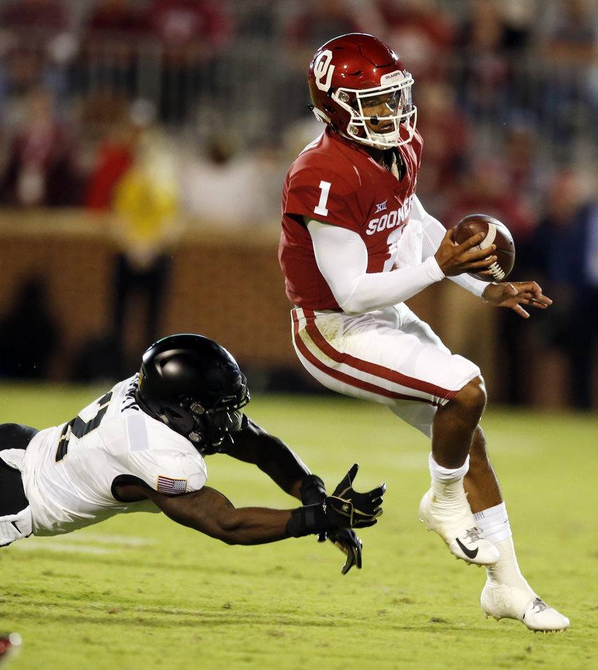 Photo - Oklahoma's Kyler Murray (1) avoids a tackle by Army's James Gibson (2) during a college football game in which the University of Oklahoma Sooners (OU) defeated the Army Black Knights 28-21 at Gaylord Family-Oklahoma Memorial Stadium in Norman, Okla., on Saturday, Sept. 22, 2018. Photo by Steve Sisney, The Oklahoman
