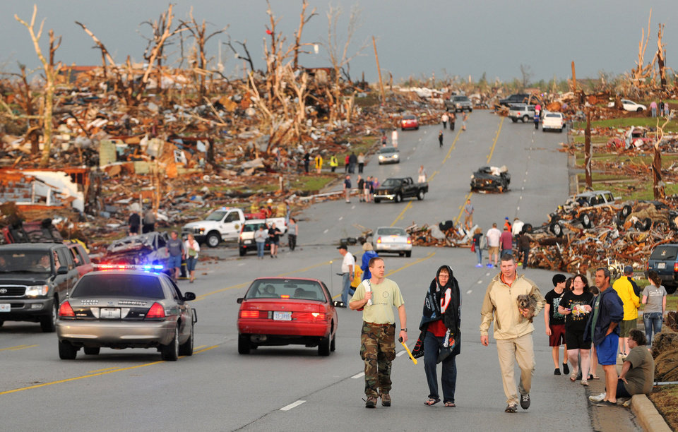 Photo - Residents of Joplin, Mo, walk west on 26th Street near Maiden Lane after a tornado hit the southwest Missouri city on Sunday evening, May 22, 2011. The tornado tore a path a mile wide and four miles long destroying homes and businesses. (AP Photo/Mike Gullett) ORG XMIT: MOMG101