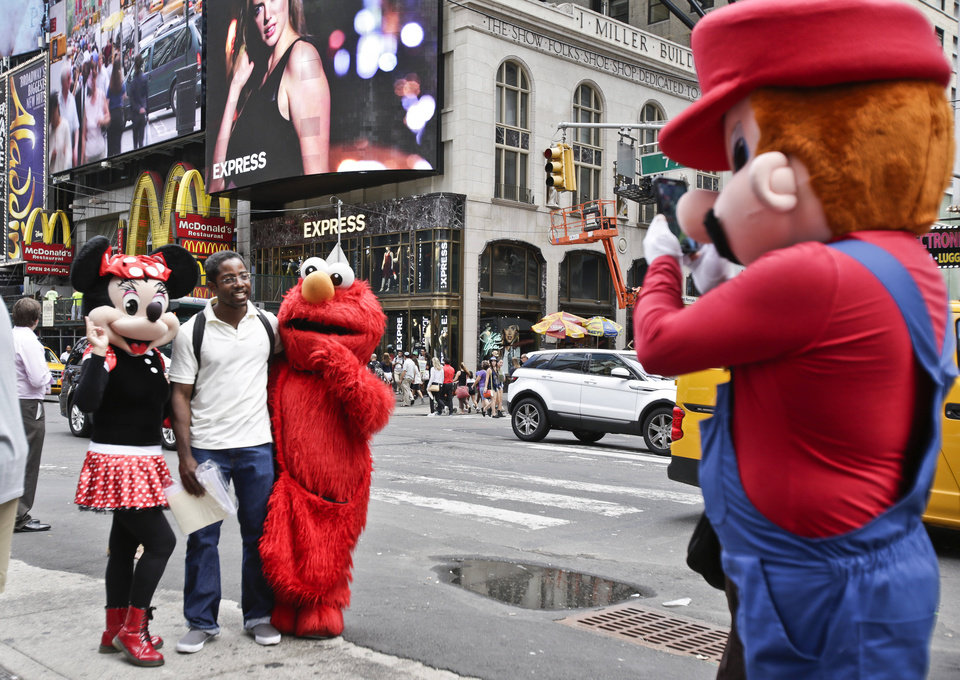 Photo - A visitor to Times Square poses for photos with iconic costumed characters, Monday, July 28, 2014, in New York. New York Mayor Bill de Blasio said Monday that he believes the people wearing character costumes in Times Square should be licensed and regulated. (AP Photo/Rachelle Blidner)
