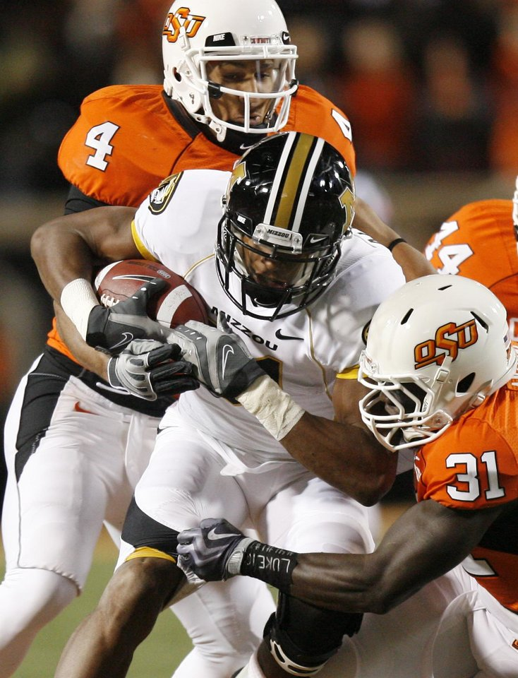 Photo - Patric Levine (4) and Lucien Antoine (31) wrap up Danario Alexander (81) during the college football game between Oklahoma State University (OSU) and the University of Missouri (MU) at Boone Pickens Stadium in Stillwater, Okla. Saturday, Oct. 17, 2009.  Photo by Sarah Phipps, The Oklahoman